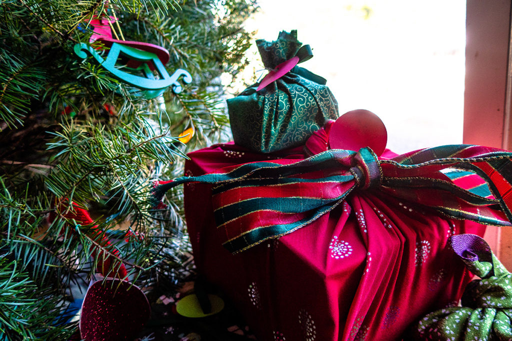 Gifts next to the Christmas tree wrapped in fabric.